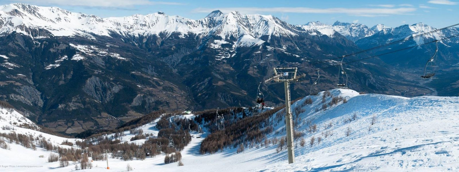 Skiers-on-chairlift-with-mountain-scenery-at-Pra-Loup-in-the-French-Alps-17941